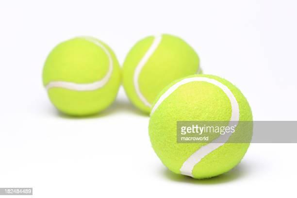 Three yellow tennis balls on a white background