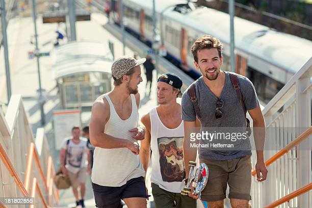 three yougn men walk from train station
