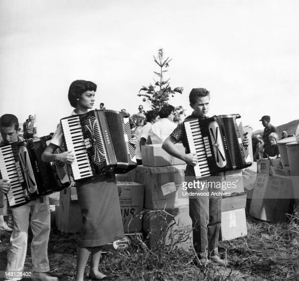 Three young accordion players perform outdoors in front of a group of people around a straggly Christmas tree and a pile of moving boxes Los Angeles...