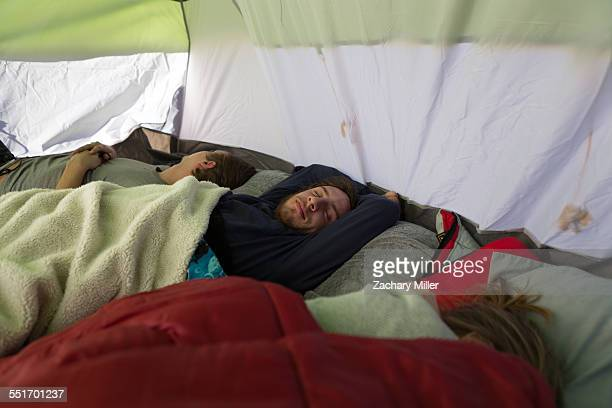 Three young adult friends asleep in tent