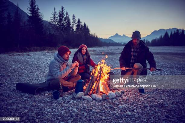 Three young adult friends preparing firewood for campfire by River Isar, Karwendel Mountains, Bavaria, Germany
