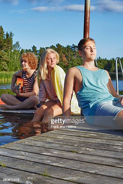 Three young adult friends relaxing on pier, Gavle, Sweden