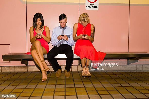 Three young adult friends texting on smartphones whilst sitting in subway station