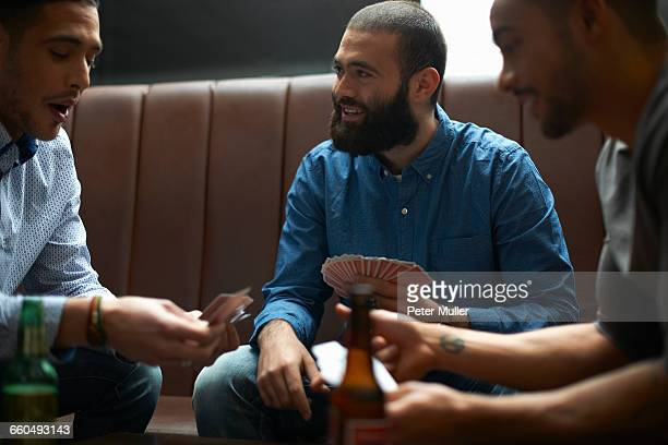 Three young adult male friends playing card game in traditional UK pub