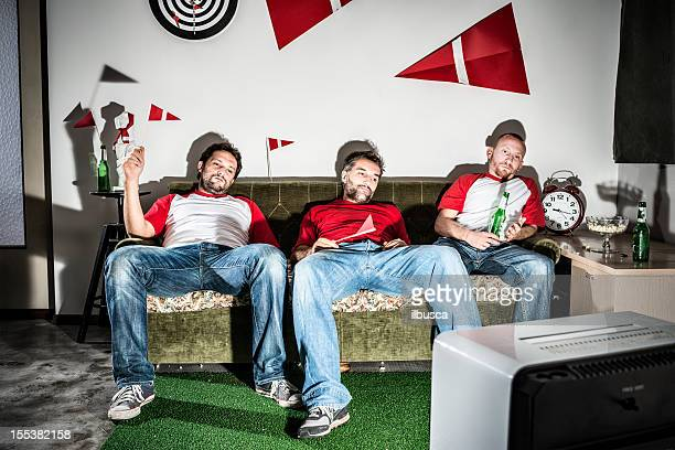 Three young adult men friends watching football on television: Defeat