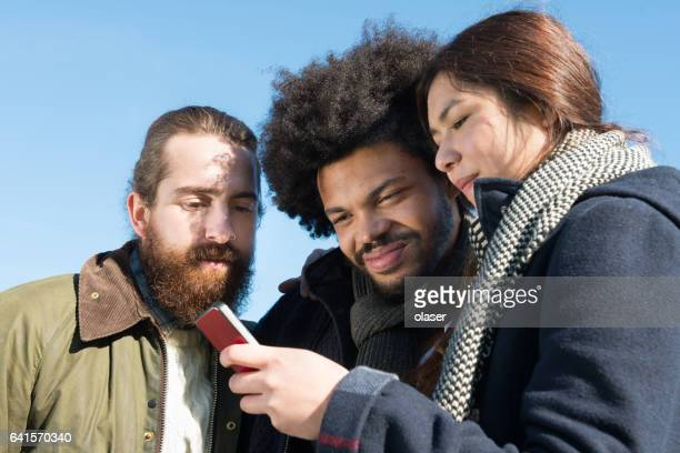 Three young adults and one mobile phone, fall clothes