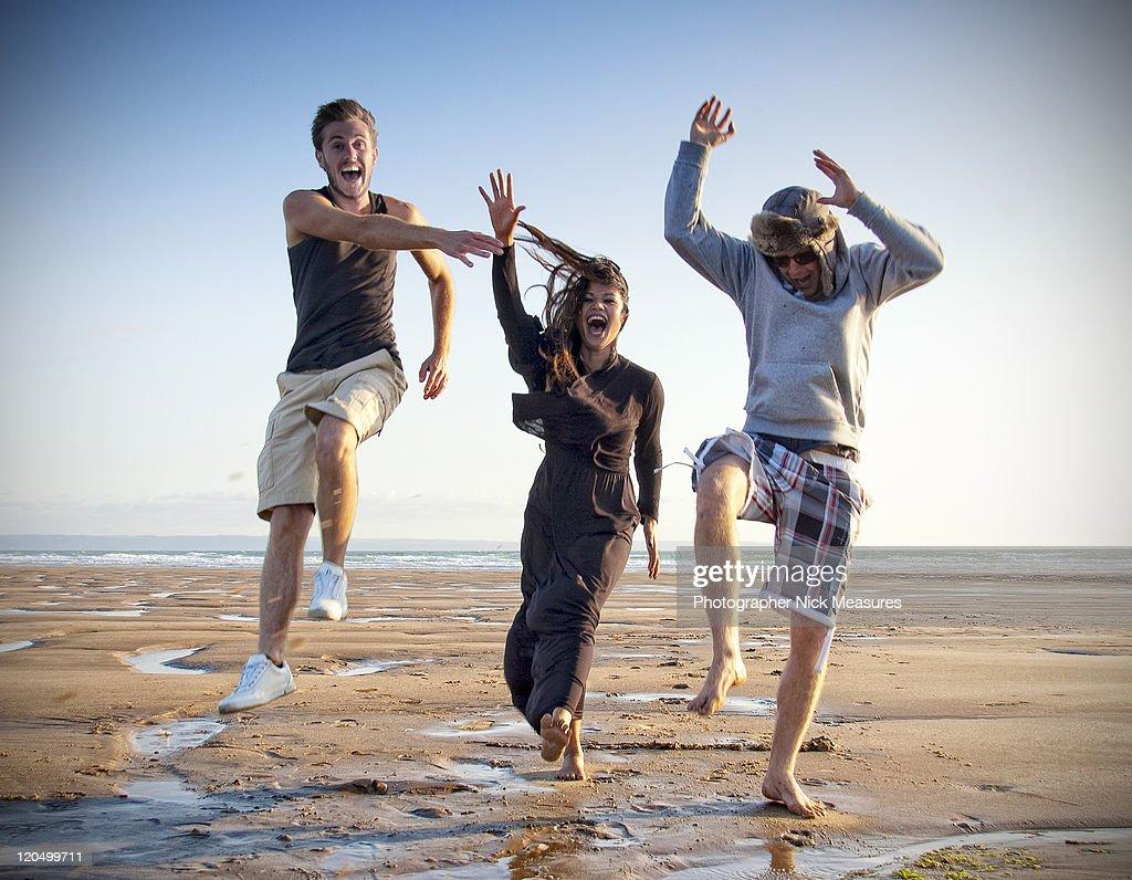 Three young adults enjoying on beach : Bildbanksbilder