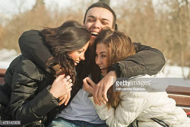 Three young adults hugging on park bench in winter