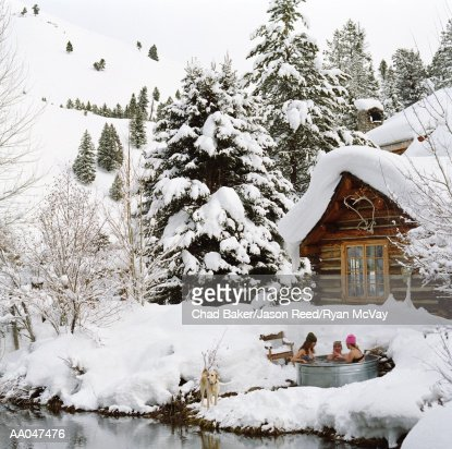 Three young adults in outdoor hot tub surrounded by snow
