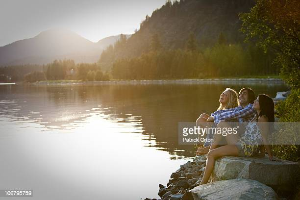 Three young adults laugh while sitting on rocks watching the sunset over the lake.