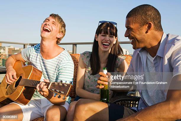 "three young adults laughing, one holding guitar - ""compassionate eye"" fotografías e imágenes de stock"