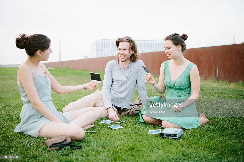 Tre giovani adulti guardando le loro foto istantanea : Foto stock