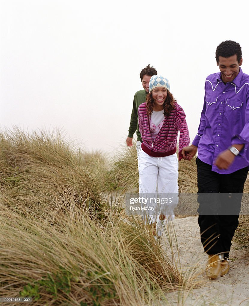 Three young adults running on sandy trail, laughing : Stock Photo