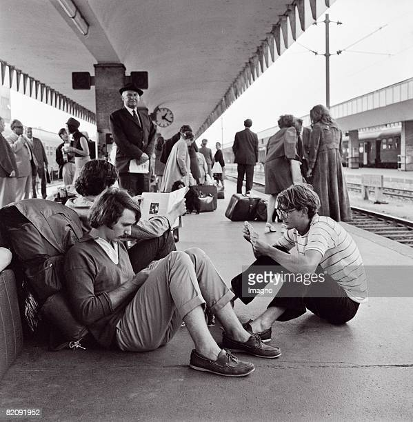 Three young adults sitting on the ground on a platform of West Station in Vienna Elder travellers in the background Photograph 1975 [Drei junge...