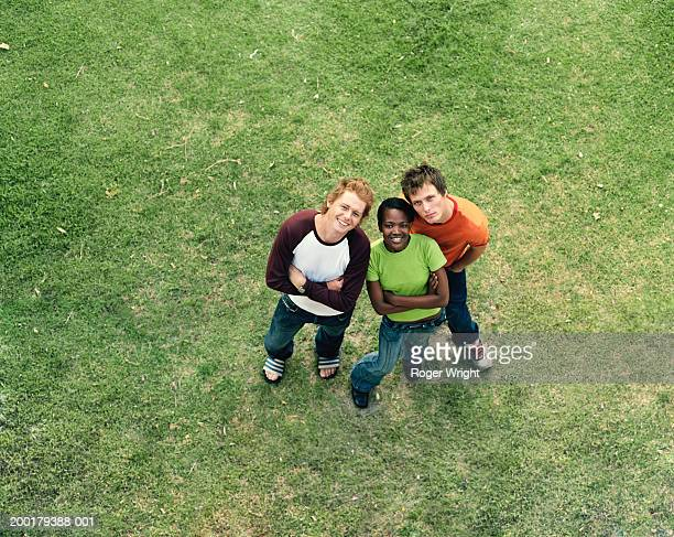 Three young adults standing on grass, smiling, portrait, elevated view