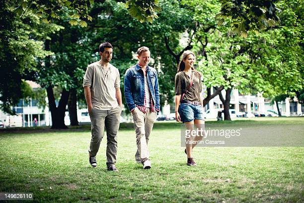 Three young adults walking in park