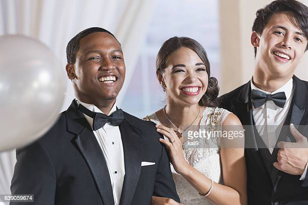 Three young adults wearing formalwear at a party