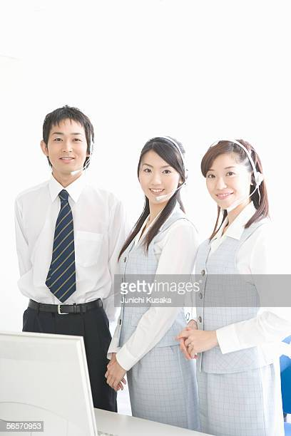 Three young adults with headsets looking at camera