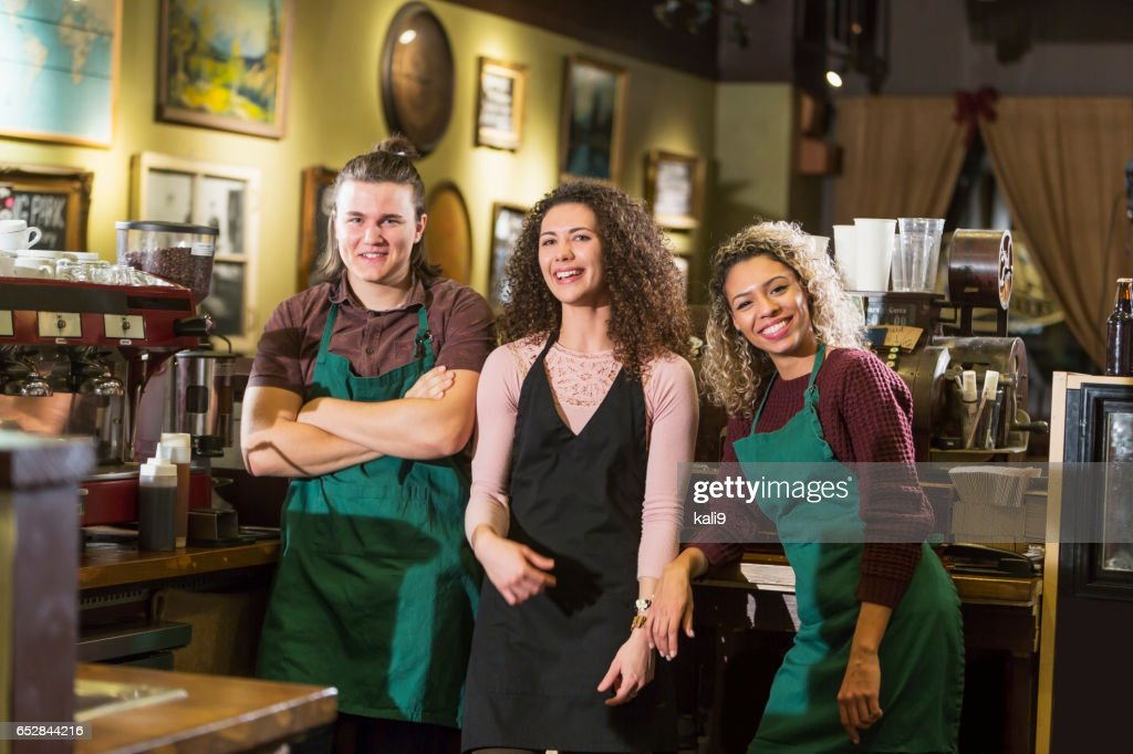 Trois jeunes adultes travaillant dans un café-restaurant : Photo