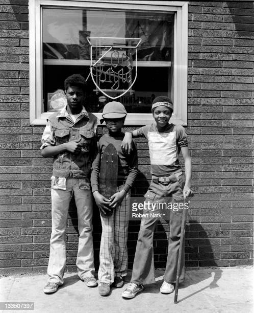 Three young African American boys pose in front of a bar window with a neon sign Chicago 1979 One by holds a skateboard to his chest while another...