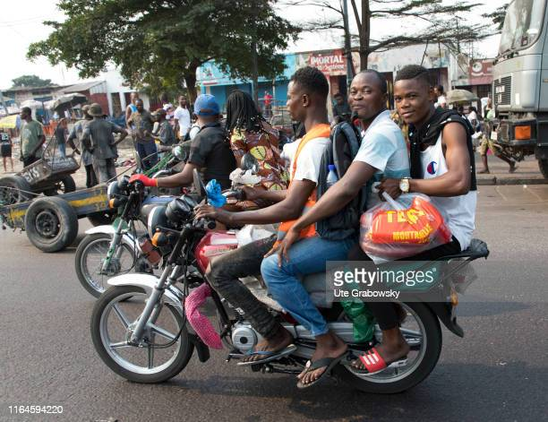 Three young African men ride together on a motorcycle Street scene in the Democratic Republic of Congo on August 15 2019 in Kinshasa Congo
