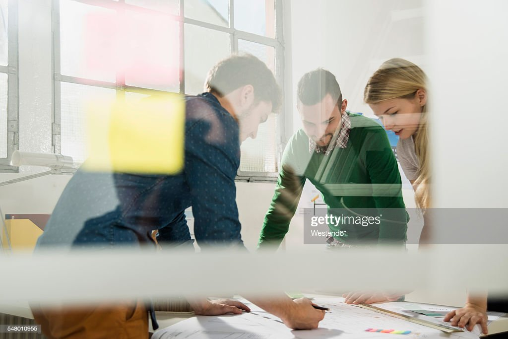 Three young architects in office discussing : Stock-Foto