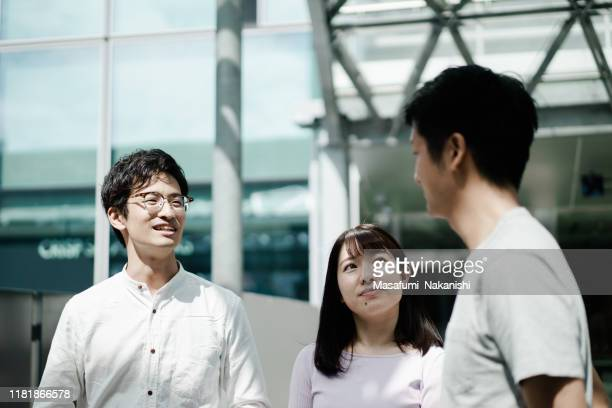 会話を楽しむ3人の若いアジアの男女 - ビジネスウェア ストックフォトと画像