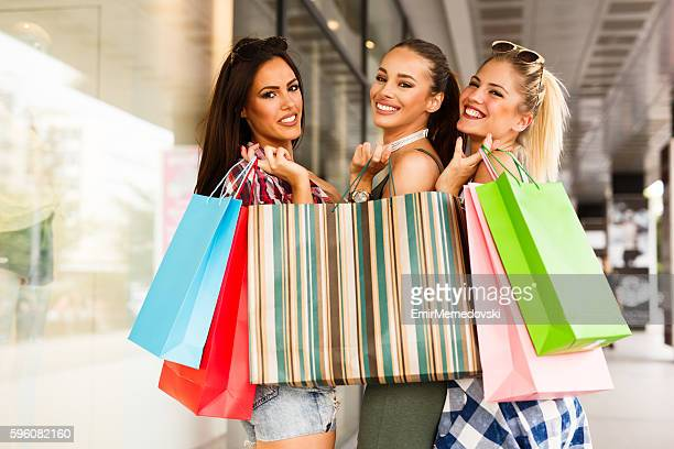 Three young attractive female friends have fun shopping together.