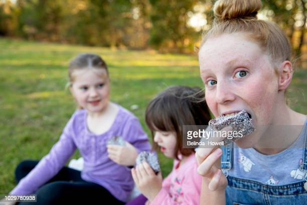 three young australian girls hanging out together, laughing and eating lamingtons. - up do stock pictures, royalty-free photos & images
