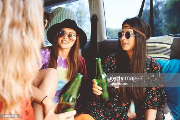 Three young boho women relaxing in recreational van