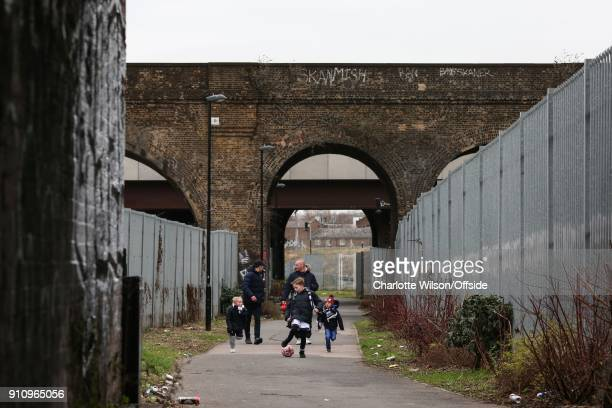 Three young boys and their dads play football beneath the arches of a railway bridge as they make their way to the match ahead of The Emirates FA Cup...