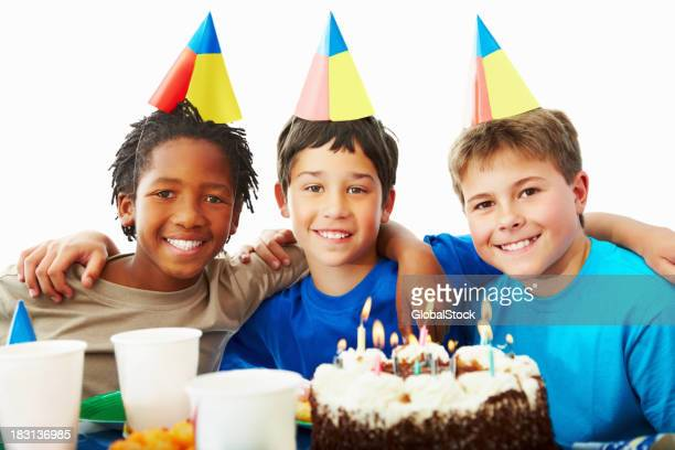 Three young boys celebrating birthday party with a cake