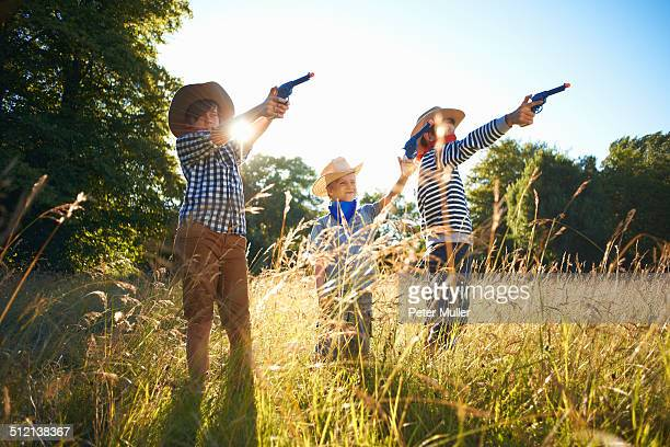 Three young boys dressed as cowboys, holding toy guns