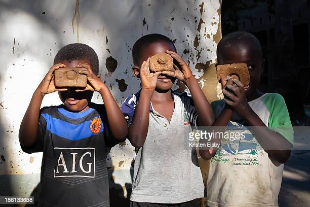 CONTENT] Three young boys in Utende village on Mafia Island pretend to take 'photographs' with their freshly made clay 'cameras'