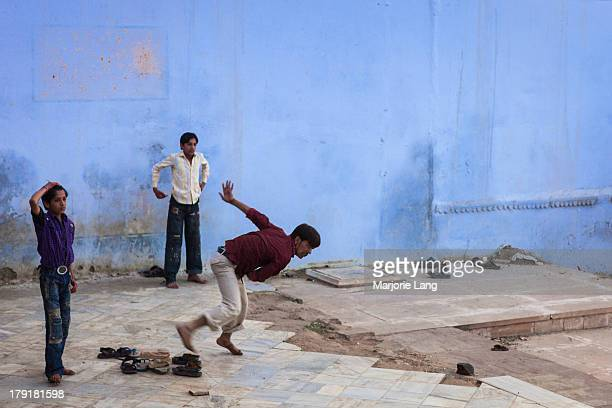 Three young boys playing cricket in a colorful blue street of Pushkar in Rajasthan, India.