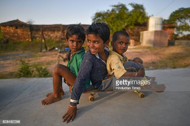 Three young boys riding on a single skateboard at Skating Park popularly known as Janwaar Castle on October 26 2016 in Janwaar India Thanks to a...