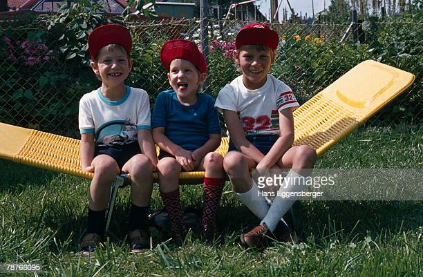 three young boys sitting on a deck chair - adjust socks stock pictures, royalty-free photos & images
