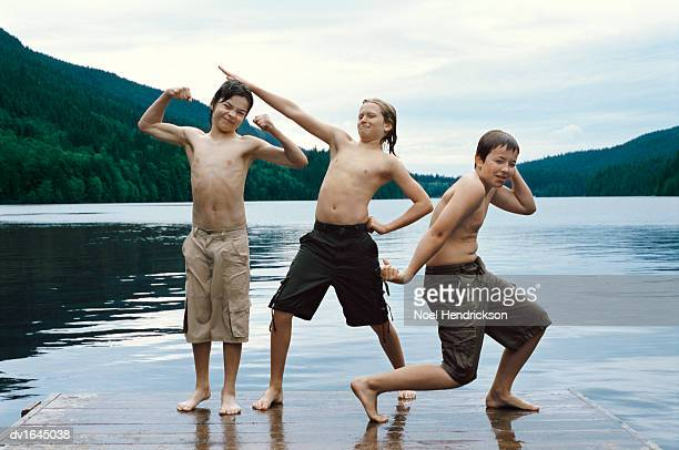 Three Young Boys Stand on a Boardwalk By a Lake, Pulling Funny Faces and Posing
