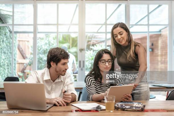 three young brazilian business people looking together on tablet