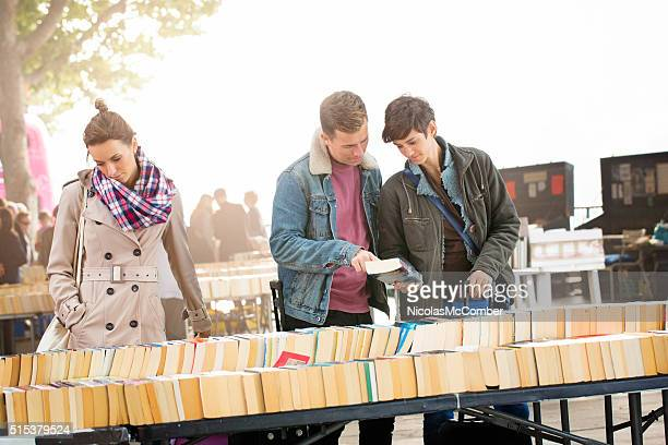 Three young British people shopping for books outdoors