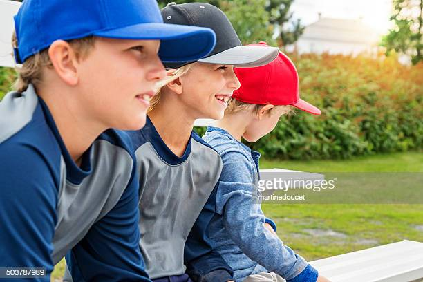 Three young brothers watching baseball game outdoors.
