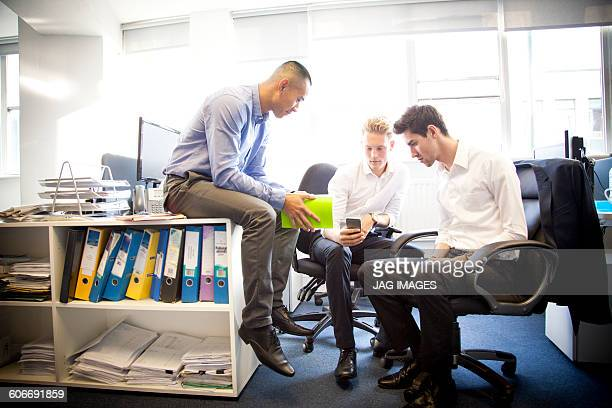 Three young business men talking in modern office