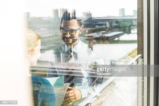 Three young business people talking behind window pane