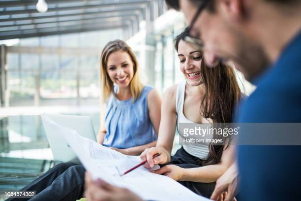 Three young business people talking together, using laptop and paper documents.