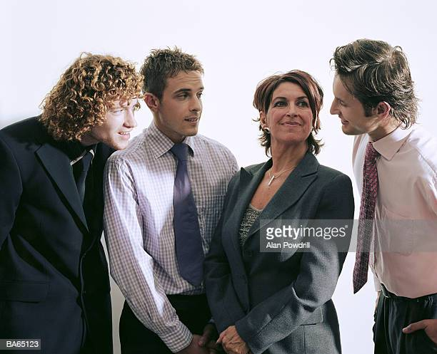 Three young businessmen looking at mature businesswoman