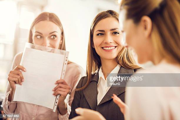 Three young businesswomen gossiping about someone.