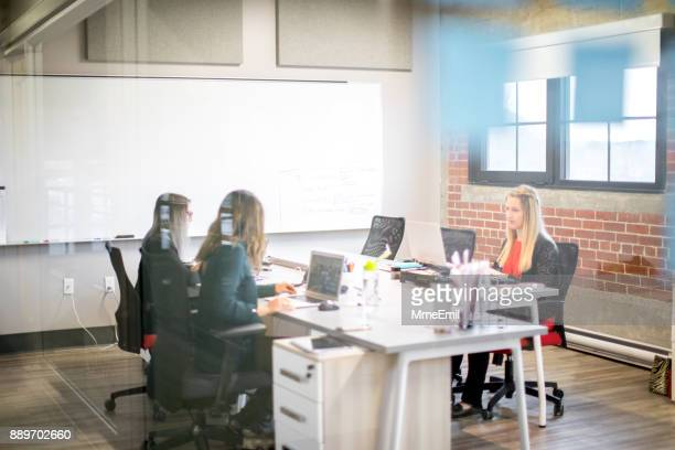 Three young businesswomen sitting at a desk and using a laptop. Office worker. Concentration, focus. Startup. Millennials. Women working together.