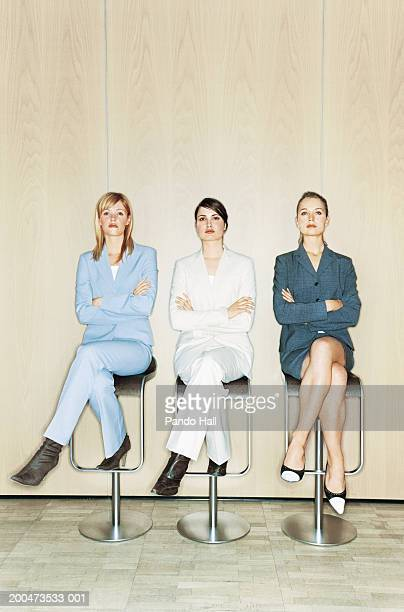 Three young businesswomen sitting on stools, arms folded