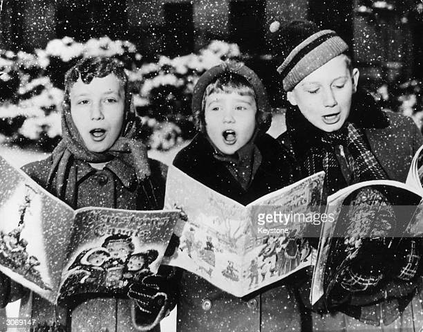 Three young carol singers give their rendering of a Christmas song in the falling snow