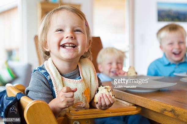 three young children eating cake at tea table - vorschulkind stock-fotos und bilder